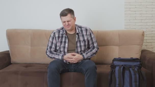 A középkorú férfi ül egy kanapén, és birtokolja a gyomrát, a nyomorban a fájdalom. Mellette a kanapé egy nagy turisztikai hátizsák.