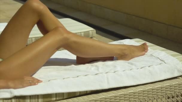 Egy nő fekszik egy nyugágyon a teraszon, a lába, mozgó, napozás és szolárium