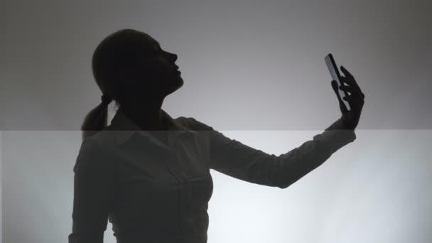 Silhouette einer Frau auf weißem Hintergrund. Eine Frau fotografiert sich mit einer Kamera im Smartphone.