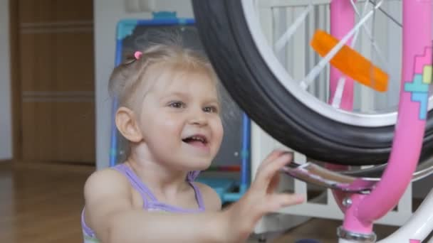 A little girl sitting in the childrens room playing with the bike, turning the wheel.