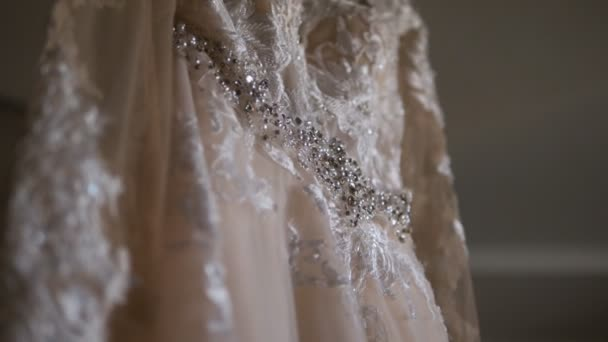 Close-up of hanging wedding dress ivory embroidered with rhinestones.