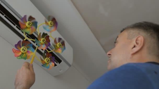 ein erwachsener Mann steht vor der Klimaanlage und hält ein Kinderspielzeug mit einem rotierenden Propeller.