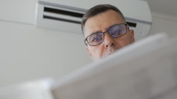 Ein Mann mit Brille steht neben einer funktionierenden Klimaanlage und studiert die Bedienungsanleitung des Geräts.
