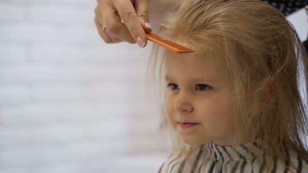 Kadeřník stylistka dělá účes pro roztomilou holčičku v kadeřnictví krásy. Kadeřnictví, stříhání vlasů.