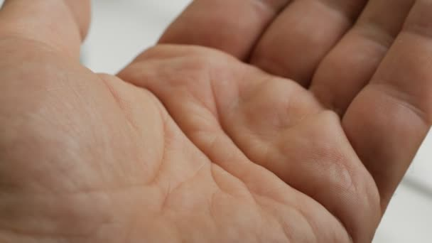 Closeup of hand holding variety of white pills on palm. Man takes pills vitamins or drugs tablets in hand.