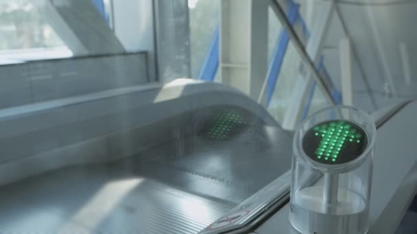 Close-up shot of indicator with blinking green arrow on working escalator. Sign allowing to pass.