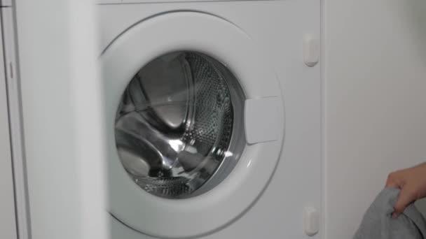 Nahaufnahme der Hand eines Mannes, der die Tür der Waschmaschine öffnet und sie mit schmutziger Wäsche belädt