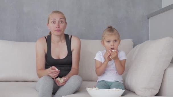 Egy nő és egy kislány ülnek egy puha kanapén, popcornt esznek és a TV-t nézik..