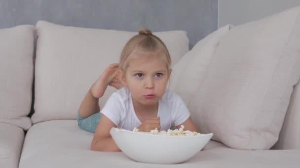 Egy kislány egy puha kanapén popcornt eszik, nézi a TV-t..