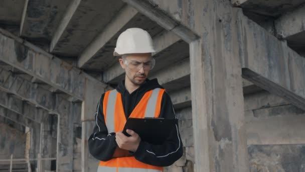 Stavitel stojící v budově ve výstavbě si dělá poznámky na tablet.