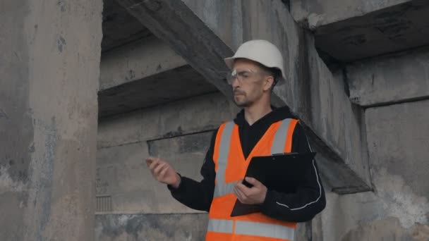 Stavební dělník kontroluje zchátralou budovu