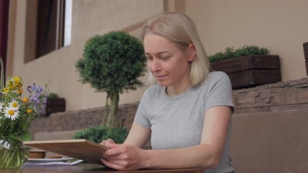 Egy nő étlapot olvas, miközben egy asztalnál ül az étterem nyári teraszán.