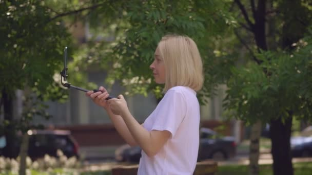 A woman using a smartphone is broadcasting live while walking in a Park.