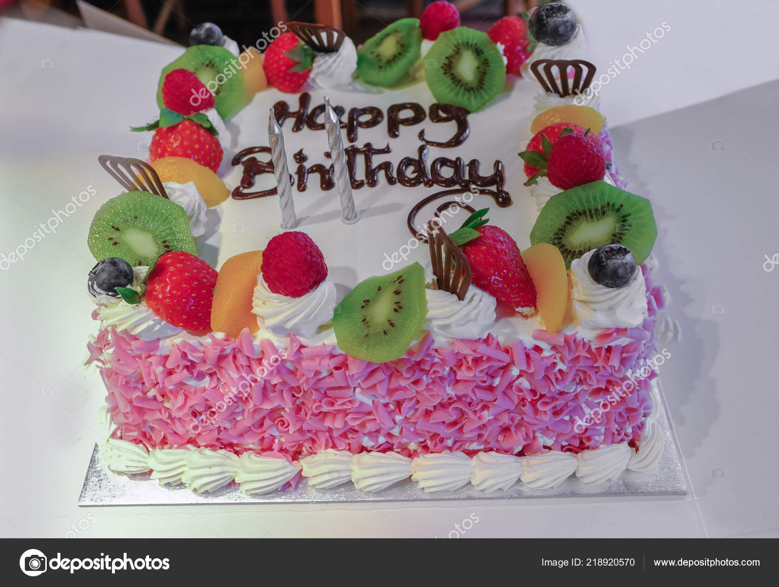 Cream Birthday Cake With Fresh Fruit On The Top And Pink Flakes Decorating Sides Happy Is Written In Chocolate Icing Two Silver Candles