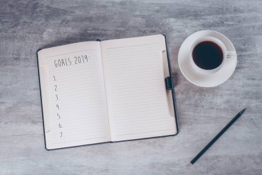 Business or planning concept: Top view image of open notebook, goals for 2019 year and coffee cup on grey table background.