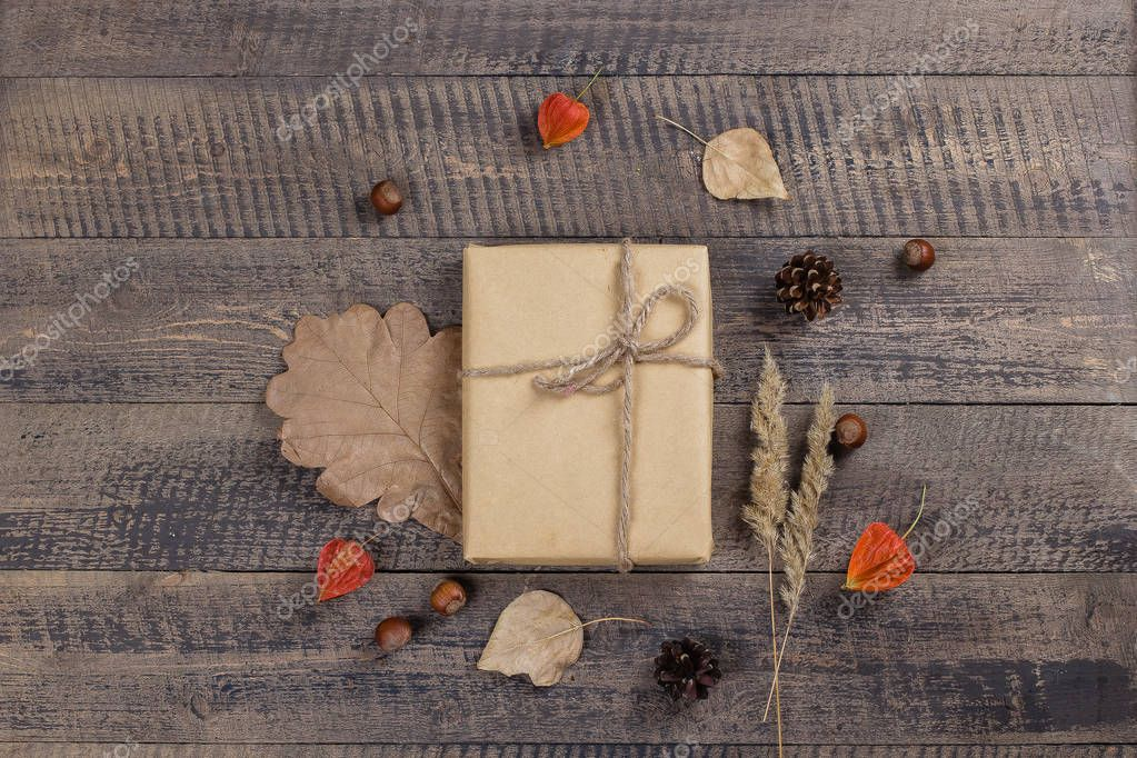Autumn composition. Gift or Present box, autumn leaves, physalis, pine cones on brown rustic wooden background. Flat lay, top view, copy space