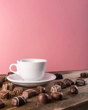 Beautiful Creative Chocolate Sweets on Wooden Background. Mix of Chocolates with Coffee Cup and Pink Backdrop