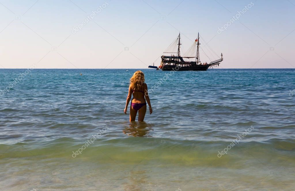 The girl is standing in the sea and looking at the medieval ship. Turkey.