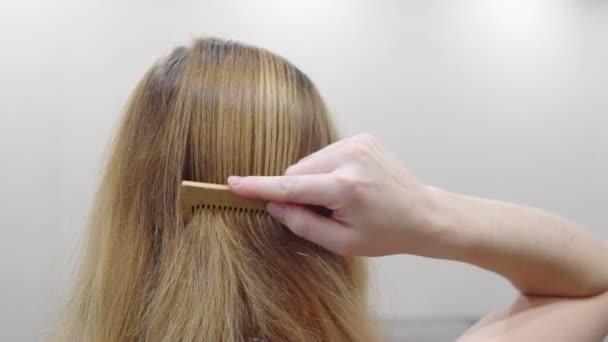 mladá dívka češe vlasy. detail