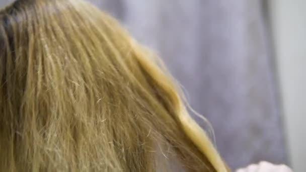 mladá dívka češe vlasy. Detail zpomalené