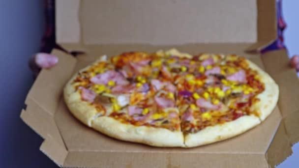 Kartónový box s pizzou uvnitř lidských rukou