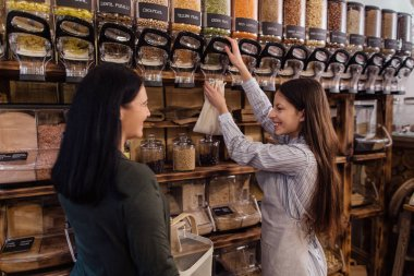 Female buying fresh raw products at package free grocery store.