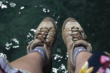 women feet over clear water