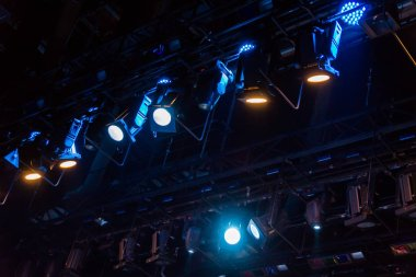 Lighting equipment on the stage of the theater or concert hall. Rays of light from the floodlights.