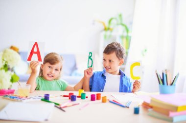 a little girl and a boy learn at home. happy kids at the table w