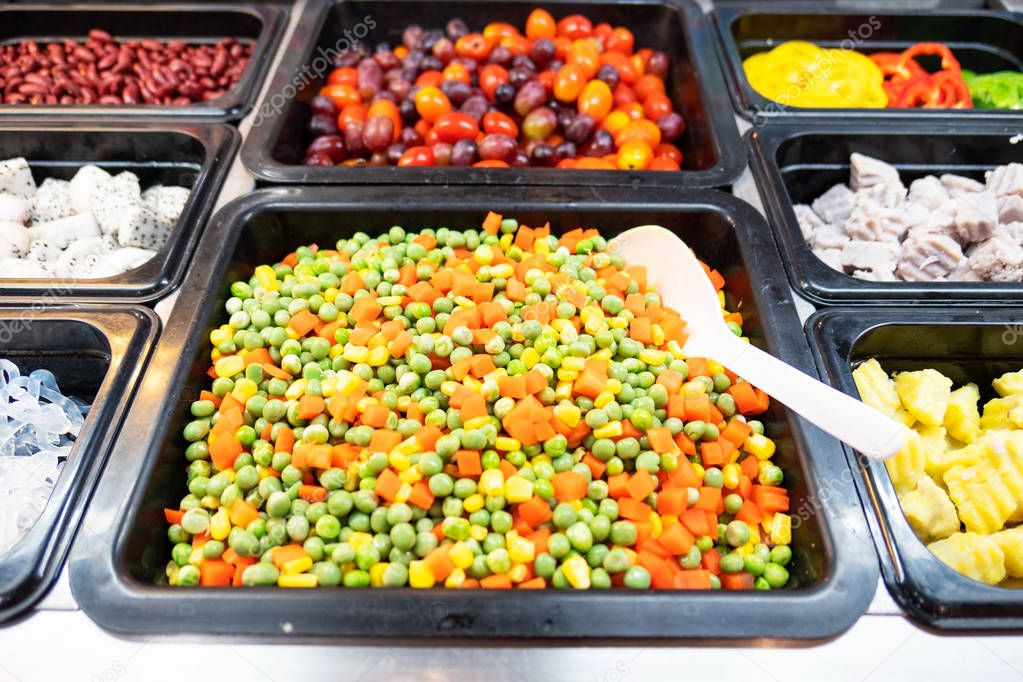 Closeup fresh salad bar with various fresh vegetables in box at supermarket for health .