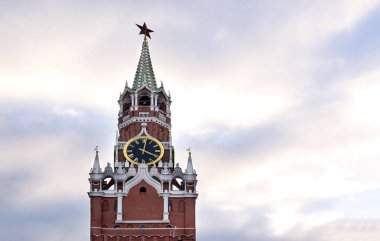 Kremlin clock tower against the sky with clouds at sunset, Moscow,