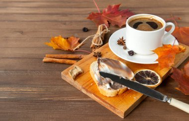 Cup of black coffee with a saucer, orange autumn maple leaves, cinnamon sticks, anise stars ,a piece of bread with creamy chocolate paste on a brown wooden background