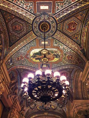 Breathtaking painted ceiling inside Opera Garnier palace in Paris France and a beautiful chandelier suspend.