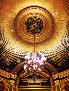 Beautiful Golden ceiling and a chandelier inside the Opera Garnier Palace in Paris, France.
