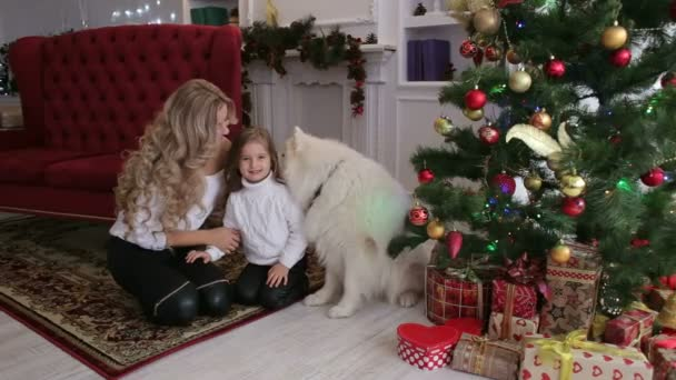 Happy family celebrates Christmas with dog at home