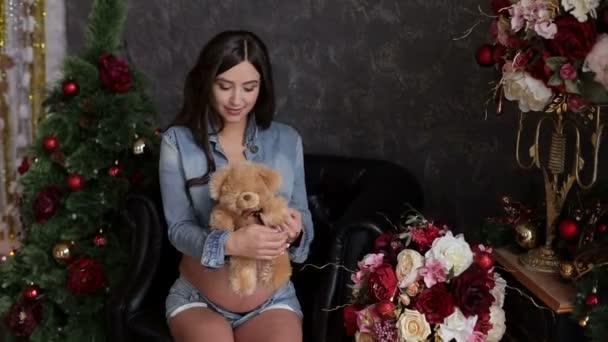 Pregnant girl with Teddy bear near Christmas tree.