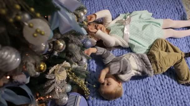 Zwei Kinder liegen auf dem Boden in der Nähe von Christmas tree.