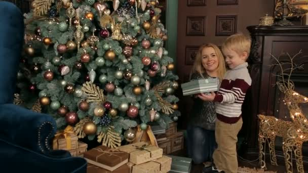 Mom gives son a Christmas gift near Christmas tree — Stock Video ...