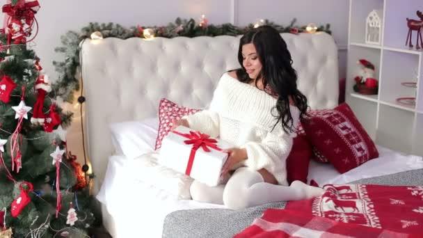 Dívka sedící na posteli s vánoční dárky