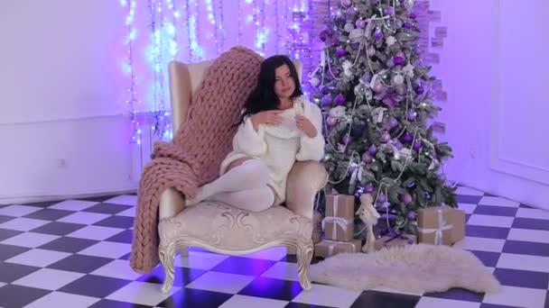 Lány ül a széken a fának a közelében pezsgővel