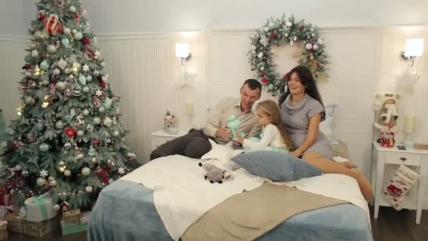 Family is lying on the bed near the Christmas tree