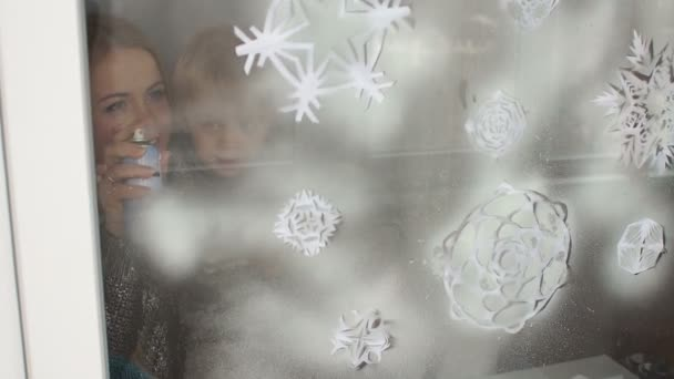 Mother and son decorate the Windows for Christmas.