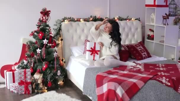 Portrét sexy dívka s vánoční dárek na posteli