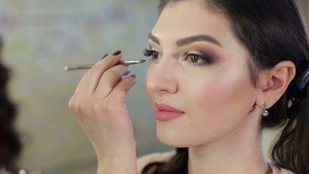 Make-up artist doing make-up for beautiful girl.