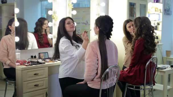Zwei Visagistinnen schminken junge Mädchen.
