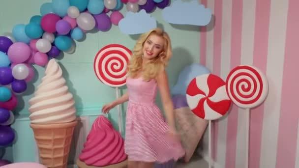 Portrét veselá tanečnice v růžové pruhované šaty a účes na pozadí v interiéru velké sladkosti candy, marshmallows, zmrzliny a balónky