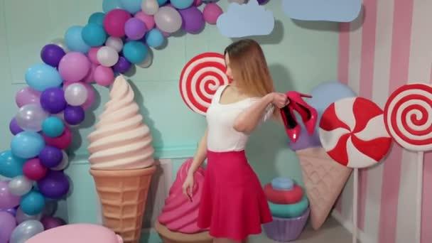 Dívka, která drží Růžové boty v ruce ve studiu