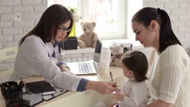Mutter und Tochter am Empfang beim Kinderarzt.