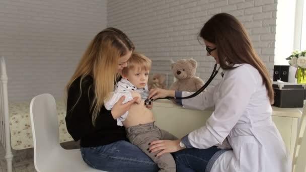 der Arzt hört einem kleinen Jungen in einem Kinderkrankenhaus mit einem Stethoskop die Lunge und das Herz ab, das Kind sitzt in den Armen seiner Mutter.