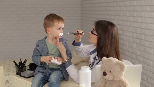 Doctor examines the throat of boy with flashlight.
